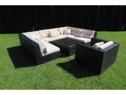 Lounge-Set Madrid besteht aus 5 Modulen: 3 Mittelteilen und 2 Eckelementen. Die Sofagruppe aus schwarzem Polyrattan runden ein Sessel und ein Couchtisch ab.