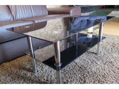 Beim rechteckigen Couchtisch Sendy ist die Tischplatte und zusätzliche Ablage aus schwarzem Sicherheitsglas. Die runden, chromfarbenen Beine aus Edelstahl bilden einen schönen Kontrast.