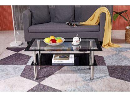 Der rechteckige Couchtisch Sendy hat eine Tischplatte aus transparentem Sicherheitsglas mit einer schwarzen Umrandung. Die zusätzliche Ablage ist aus schwarzem Sicherheitsglas. Die Beine sind aus Edelstahl.