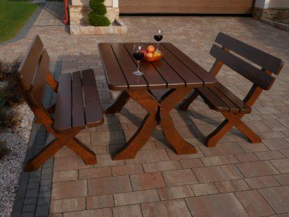 ein Tisch und zwei braune Bänke im bayerischen Stil stehen auf der gepflasterten Auffahrt vor dem Haus